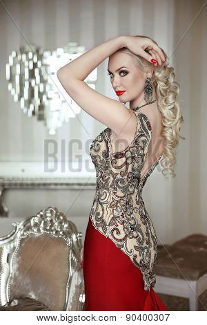 Beautiful Blond Woman Model Posing In Elegant Dress With Makeup And Hairstyle At Modern Interior. In
