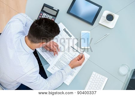 Office Worker Filling Out Contract Documents.