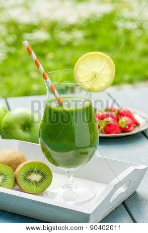 A Green Smoothie On A Wooden Tray