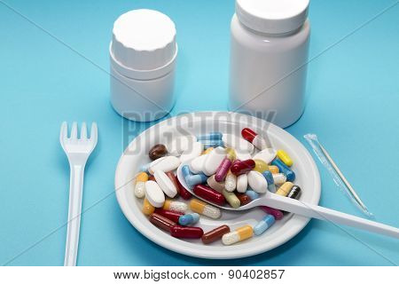Different pills on a plate with two bottle