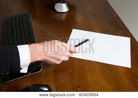 Businessman Holding A Pen Over A Blank Paper Sheet
