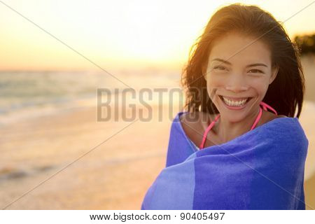 Bathing beach woman with towel happy portrait. Young pretty mixed race Asian Caucasian girl wrapped in towel standing in beach sunset. Smiling happy enjoying summer holiday travel vacation. Hawaii.
