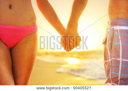 Beach sunset couple in love holding hands romantic on honeymoon. Bikini girl and casual beachwear man newlyweds people standing on travel summer vacations on tropical beach.