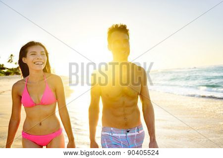Beach Lifestyle Couple Walking on Beach at Sunset enjoying healthy active lifestyle in summer sun. People in beachwear, woman in bikini and man in casual swim shorts.