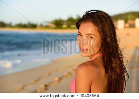 Portrait of beautiful mixed race woman on beach looking at camera. Multicultural Asian Caucasian female in bikini on North Shore of Oahu, Hawaii, USA.