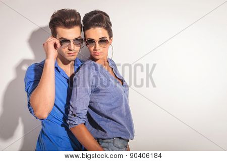 Casual man fixing his sunglasses while his lover is leaning on him, both looking down.