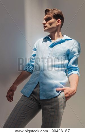 Side view of a casual young man looking away from the camera while holding one hand in his pocket.