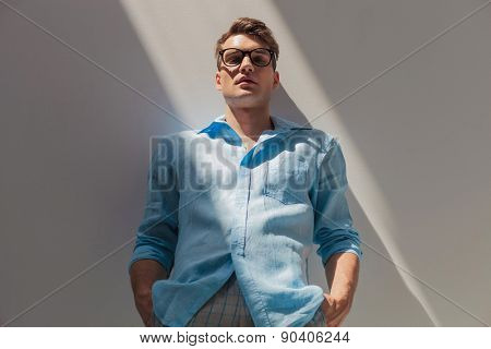Attractive casual man leaning on a wall with his hands in pockets, looking at the camera.