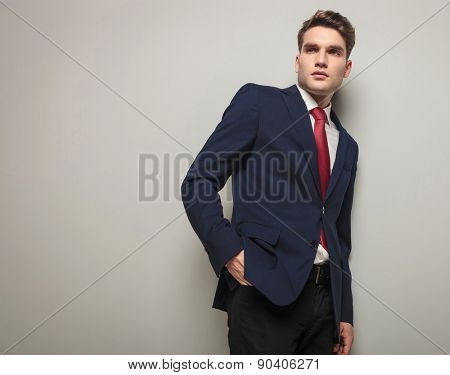 Side view of a young business man looking away from the camera while leaning on a grey wall.