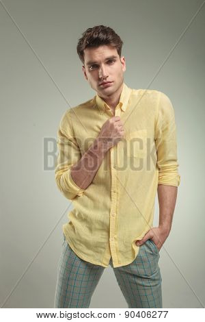 Young casual man standing on studio background with his hand in pocket while opening his shirt.