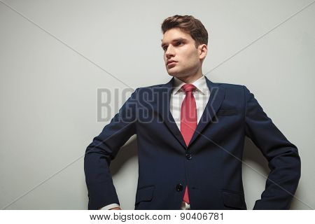 Down view of a handsome business man leaning on a wall while looking away from the camera in a super hero pose.