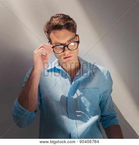 Young fashion man looking at the camera while putting on his glasses.