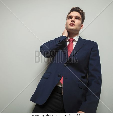 Concerned business man looking away from the camera while holding one hand to his neck.