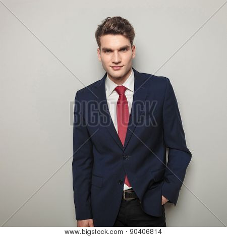 Handsome business man holding his hand in pocket while smiling to the camera.