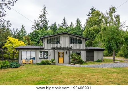 Mid-century modern cottage house in the woods. Home exterior design.