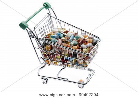 Shop cart with different colorful pills on white
