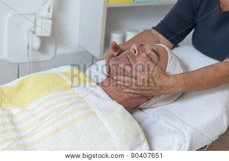 Man At Beauty Center Receiving Facial Treatment