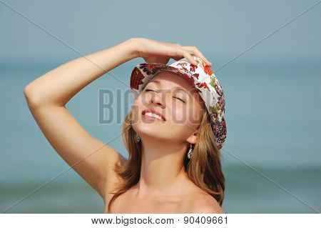 Young smiling  woman in hat with close eyes tans