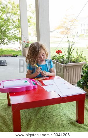 Cute Little Girl Coloring In On An Outdoor Patio