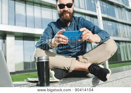 Young Hipster In Sunglasses Making Selfie With Coffee Outdoors