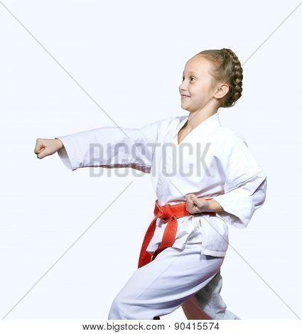 Sportswoman with red belt is beating blow arm