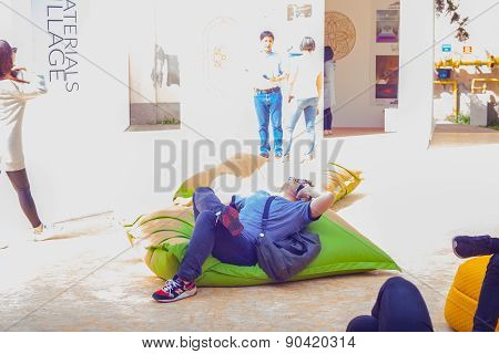 Young Man Talking On Smartphone While Lying On Green Pouf