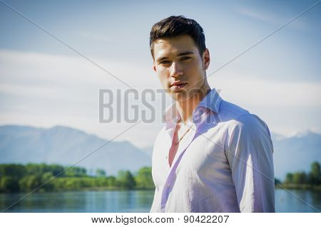 Handsome young man on a lake in a sunny, peaceful day