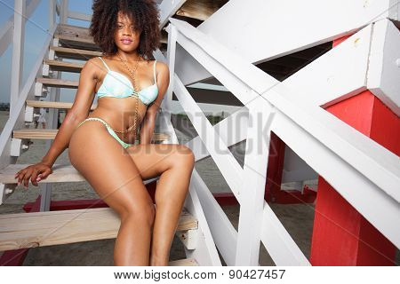 Woman posing by a lifeguard hut on the beach