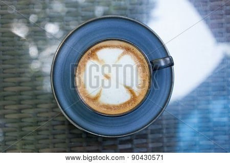 A Cup Of Coffee With Flower Pattern In A Blue Cup On Mirror