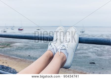 Woman Resting Feet On Railing By The Sea