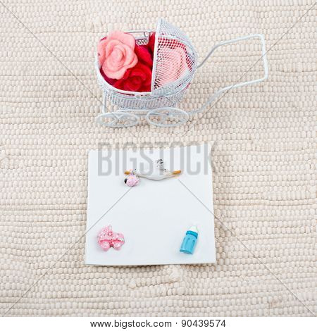 Baby card - baby shower theme. Pram full of flowers on white textile background and a blank signboar