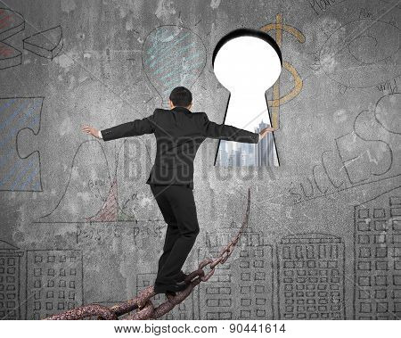 Man Balancing On Old Iron Chain Toward Keyhole With Cityscape