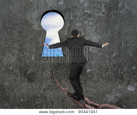 Man Balancing On Old Iron Chain Toward Keyhole With Sky