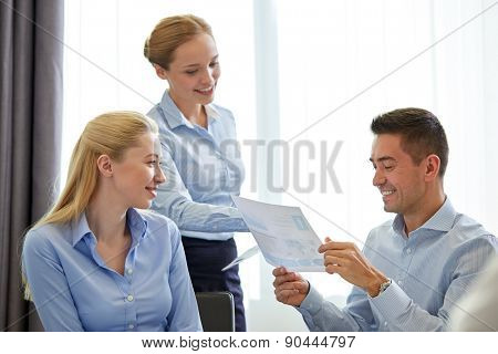 business, people, meeting and teamwork concept - smiling businesswoman giving papers to man in office