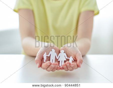 people, charity and care concept - close up of happy girl hands holding paper family cutout at home