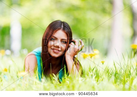 Young beautiful woman with apple resting on fresh green grass with flowers