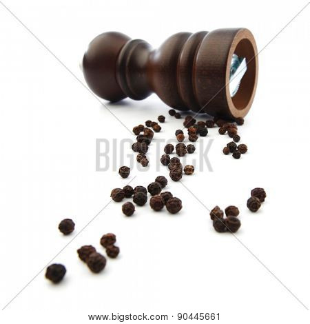 Wooden peppermill with peppercorns isolated on white background