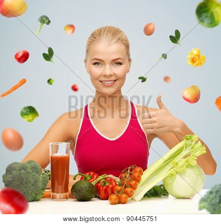 people, healthy eating, vegetarian and health care concept - happy woman with organic food and falling vegetables showing thumbs up over gray background