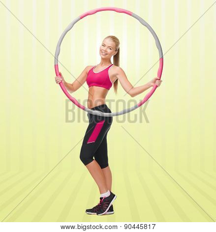 fitness, sport, people and healthcare concept - young sporty woman exercising with hula hoop over yellow striped background