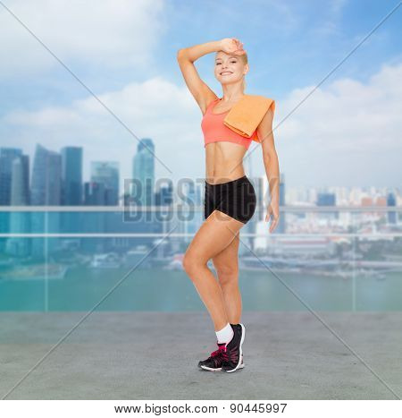sport, fitness, people and workout concept - smiling sporty woman with towel wiping off sweat over city waterside background