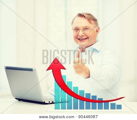 technology, oldness, people, success and business concept - old man in eyeglasses with laptop computer showing thumbs up over office background and growth chart