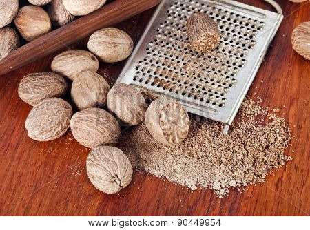 Ground nutmeg grated on wooden table background