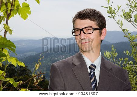 portrait of a young happy businessman with glasses, outdoors
