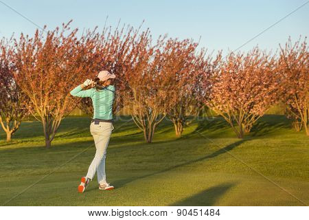 Female golf player teeing-off during dusk.