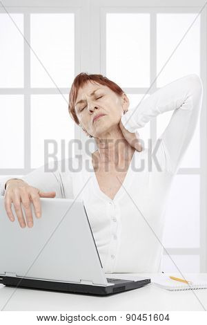 Sixty years woman at work with neck pain