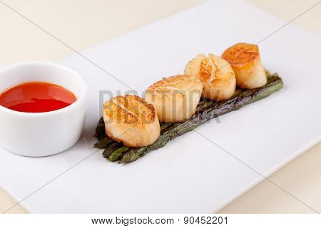 fried scallops with asparagus on a white plate and sauce