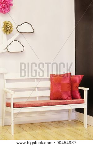 White bench with red pillows