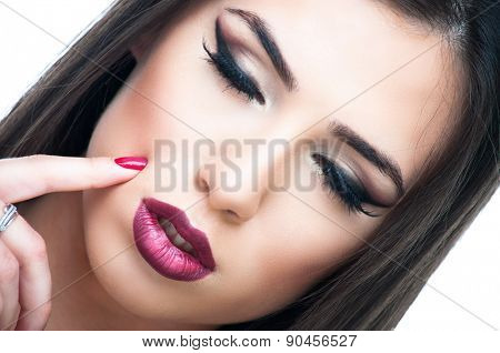 Close up shot of a beautiful brunette with closed eyes and finger on her face