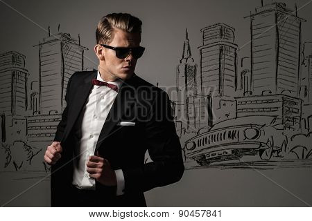 Sharp dressed man in black suit against city panorama drawing