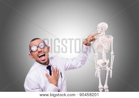 Funny doctor with skeleton isolated on white